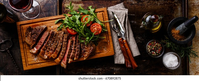 Sliced grilled beef barbecue Striploin steak and salad with tomatoes and arugula on cutting board on dark background