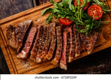Sliced grilled beef barbecue Striploin steak and salad with tomatoes and arugula on cutting board close-up