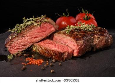 Sliced grilled beef steak with spices on slate slab on dark background