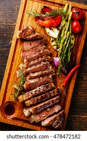 Sliced grilled Black Angus Steak Striploin and vegetables on cutting board close up