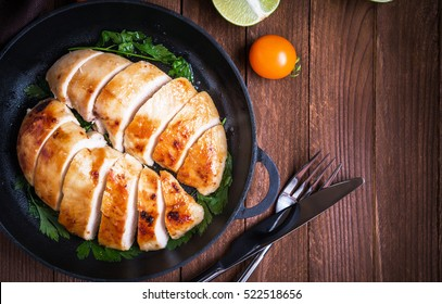 Sliced grilled chicken breasts with lime and parsley on dark wooden background top view. Healthy food. Nutritious meal.