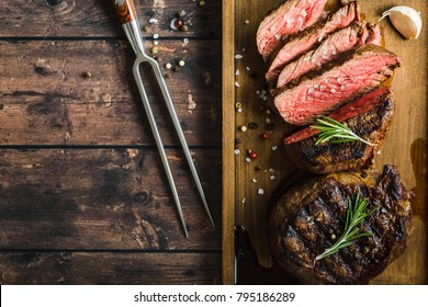 Sliced grilled marbled meat steak Filet Mignon, seasonings, fork, wooden cutting board. Space for text. Juicy meat steak. Beef steak grilled/fried. Top view. Roasted meat steak. Close-up. Rustic