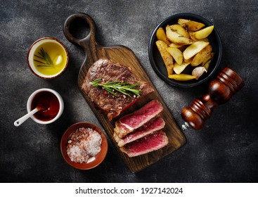 Sliced grilled meat steak New York Striploin with sauce and potato on wooden board on grey background. Top view. Medium rare meat