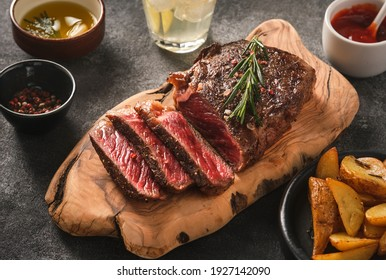 Sliced grilled meat steak New York Striploin with sauce and potato on wooden board on grey background. Barbecue steak. Medium rare meat