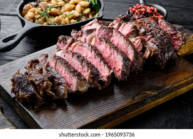 Sliced grilled meat steak Rib eye medium rare set, on wooden serving board, with white beans and rosemary in cast iron pan, on black wooden table background