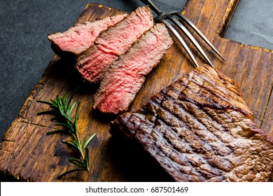 Sliced grilled medium rare beef steak served on wooden board Barbecue, bbq meat beef tenderloin. Top view, slate background.