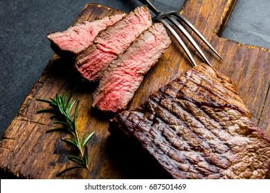 Geschnittenes gegrilltes, mittleres, seltenes Rindfleisch Steak, serviert auf Holzbrett Barbecue, bq Fleisch Rindfleisch Tenderloin. Draufsicht, schiefer Hintergrund.