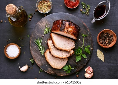 Sliced grilled pork barbecue meat on wooden cutting board over dark background, top view.
