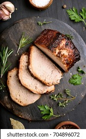 Sliced grilled pork on wooden cutting board, top view