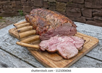 Sliced grilled rack of veal with bones on a wooden plate on a wooden table