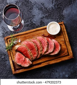Sliced grilled tenderloin Steak roastbeef and Pepper sauce on wooden cutting board and Red wine on dark background