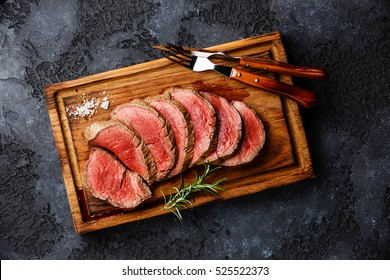 Sliced grilled tenderloin Steak roastbeef on wooden cutting board on dark background