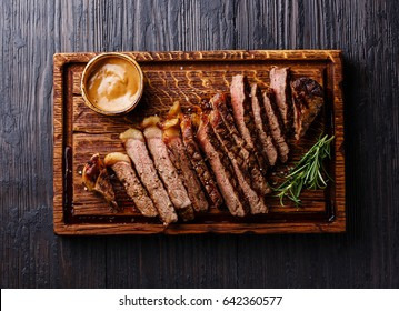 Sliced grilled well done Striploin steak with Pepper sauce on cutting board on burned black wooden background