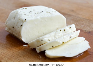 Sliced halloumi cheese with mint on wooden board in perspective.