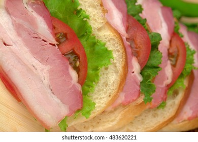 Sliced ham with bread and greens