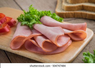 Sliced ham on wooden plate and bread slices