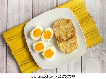 Sliced hard boiled eggs and a buttered English muffin on a white plate, which is on a yellow mat and light wood surface.