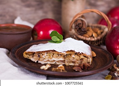Sliced homemade apple strudel served with fresh apples, cinnamon sticks and sugar powder over old wooden background. Close up, dark rustic style Apple strudel.