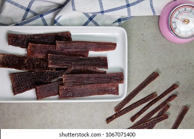 Sliced of Homemade Beef Jerky in crockery plate with napkin and timer