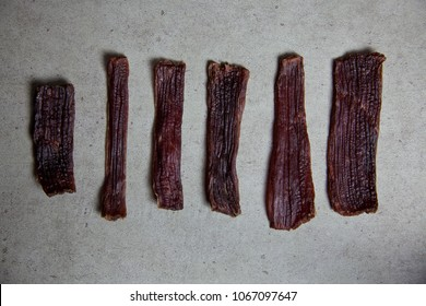 Sliced of Homemade Beef Jerky on stone textured background