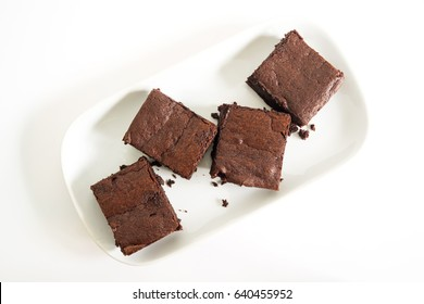 Sliced homemade brownies on white plate. Served on rectangle white plate. Favorite chocolate dessert for chocolate lover. Sweet and moist of cocoa taste. Top view.
