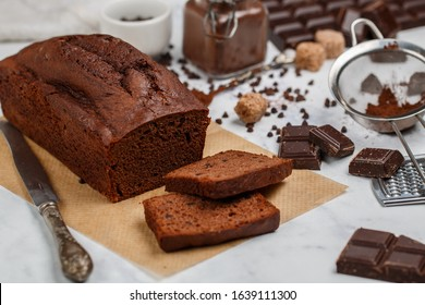 Sliced homemade chocolate banana pound cake loaf. Delicious dessert for Breakfast. A treat for tea. Ingredients on a light marble table. Selective focus