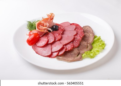 Sliced homemade dry sausages and meat products, cured meat, bacon, with fresh cucumber slices on a white plate. Isolated on white background, close-up, top view.