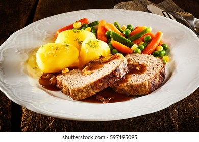 Sliced homemade roasted meat loaf with an assortment of fresh healthy vegetables and gravy in a close up view on a white plate