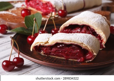 Sliced homemade strudel with cherry close-up on a plate. horizontal