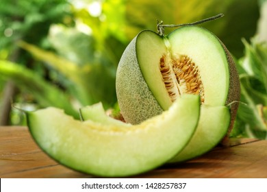 Sliced of Honeydew melons,honey melon or cantaloupe (Cucumis melo L.) on wooden table with blurred garden background.Favorite fruit in summer.Fruits or healthcare concept.Selective focus.