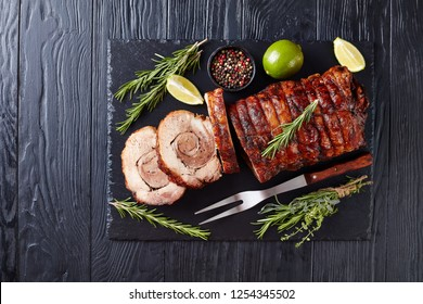 sliced hot Porchetta - delicious pork roast of Italian culinary holiday tradition, sliced Rolled pork belly on a slate tray with rosemary and lime, close-up, flatlay