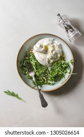 Sliced Italian burrata cheese, black pepper mill, fresh arugula salad, pine nuts and olive oil in white ceramic plate over white marble background. Flat lay, space