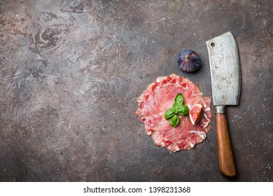 Sliced jamon with butcher knife and fig. Parma ham, hamon on wooden background with copy space, top view. Jamon Serrano, Iberico. Traditional Spanish ham