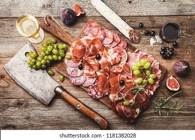 Sliced jamon on cutting board with figs, grapes and red wine. Parma ham, hamon on wooden background with copy space, top view. Jamon Serrano, Iberico. Traditional Spanish ham