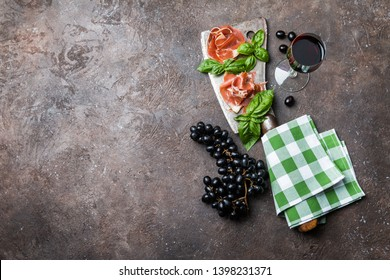 Sliced jamon on cutting board with figs, grapes and white wine. Parma ham, hamon on wooden background with copy space, top view. Jamon Serrano, Iberico. Traditional Spanish ham