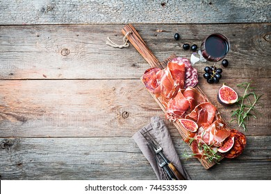 Sliced jamon on cutting board with fig?, grapes and red wine. Parma ham / hamon on wooden background with copy space, top view. Jamon Serrano / Iberico. Traditional Spanish ham