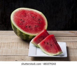 A sliced of jucie watermelon on a wooden background