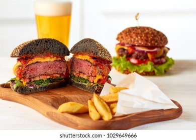 Sliced juicy burger with chips and beer