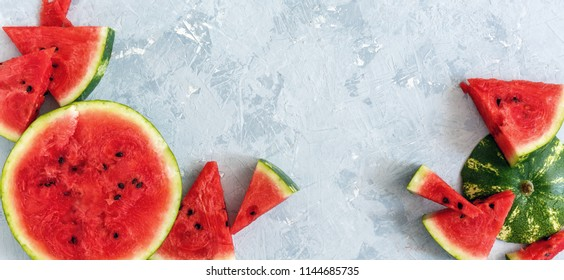 Sliced juicy watermelon on textured concrete background. Top view.