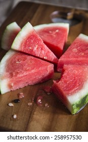 Sliced juicy watermelon on wooden chopping board in kitchen