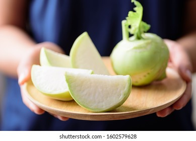 Sliced kohlrabi on wooden plate holding by hand, food ingredient