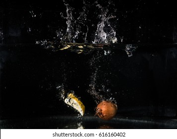 Sliced lemon falling into the water on the black background.