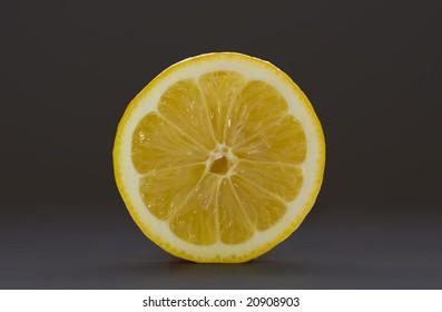Sliced lemon isolated on a dark gray background