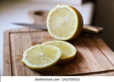 A sliced lemon on a wooden chopping board