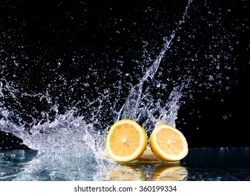 Sliced lemon in the water on black background. Fresh lemons with water splash. Dynamics of a liquid, juicy appetizing lemon and glass with splashed out water on a dark surface of a table