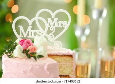 Sliced lesbian wedding cake on blurred background