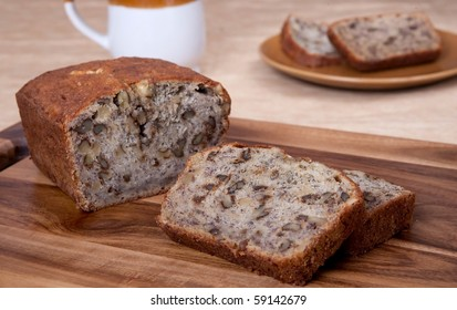 sliced loaf of banana walnut bread on a cutting board with one serving of two slices and a mug in the background