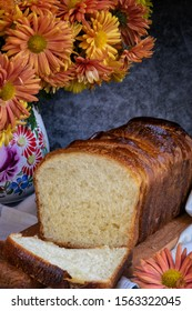 Sliced loaf of bread. Slices of brioche bread. Homemade French bread vase of autumn flowers.