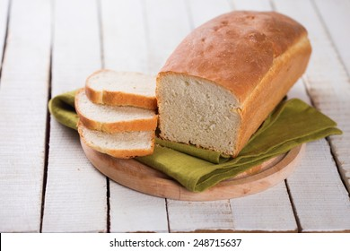 Sliced loaf of homemade  bread on board on white wooden background. Selective focus.