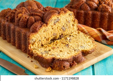 Sliced loaf of pecan pumpkin bread sitting on wooden cutting board with full loaf in background on blue wooden table